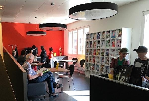 viele Leute in der Lounge der Bibliothek, lesend, redend oder Kaffee trinkend