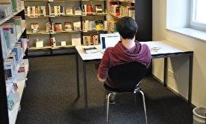 Mann sitzt vor Laptop an einem Arbeitsplatz in der Bibliothek
