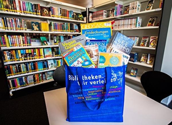 eine Tasche voller Bücher und Medien steht vor einem Büchergestell