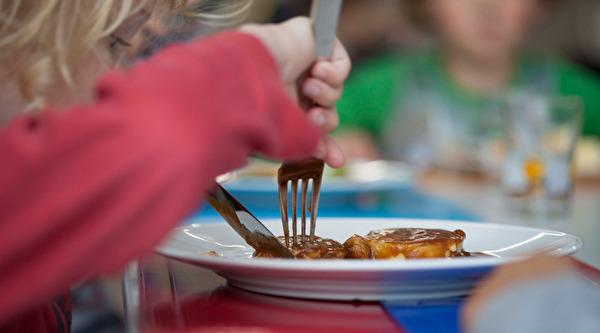 Kind schneidet im Teller sein Essen