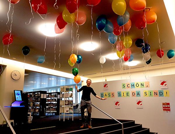 Bibliotheksleiter Roman Weibel mit bunten Begrüssungsballonen