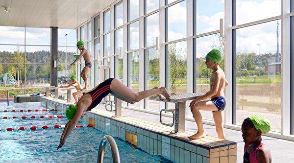 Kinder springen ins Hallenbad-Becken