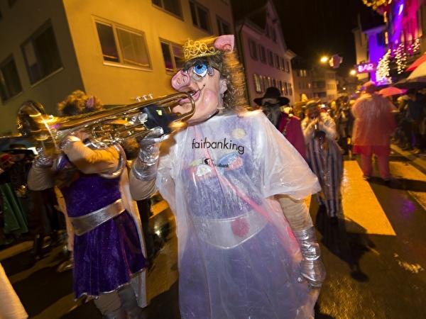 Die Altdorfer Katzenmusik schmettert den Katzenmusikmarsch mitten im Dorf. An der Spitze die Posaunen mit Schweinchenmasken, gefolgt vom langen Zug der Trompeten, Trommler und Pauken.