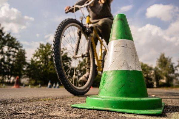 Fahrrad, das um einen Strassenkegel fährt