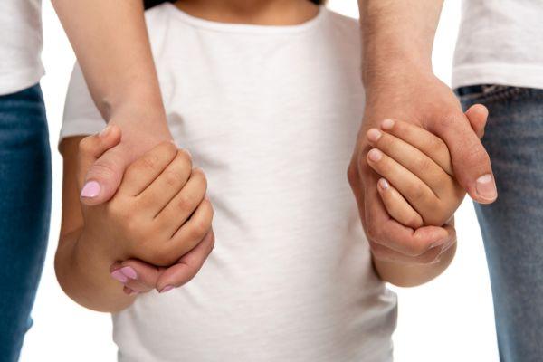 Kind an den Händen von Eltern