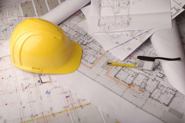 Helm liegend auf Planunterlagen