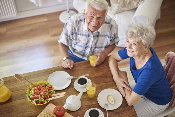 älteres Ehepaar am Tisch in der eigenen Wohnung
