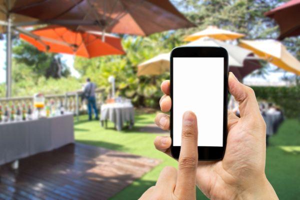 Handy im Vordergrund, Veranstaltung im Hintergrund