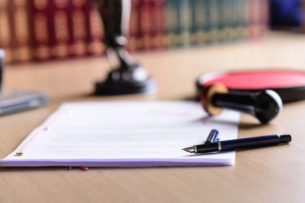Dokument mit Kugelschreiber, die vor alten Büchern liegen