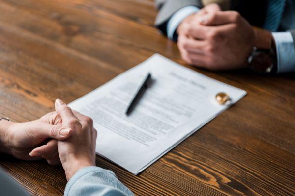 Blatt Papier zwischen vier Händen