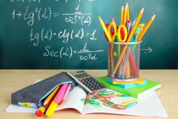 Hefte, Etui und Stifte vor einer Wandtafel