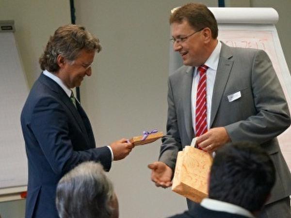 Gemeindepräsident Daniel Bichsel überreicht dem Referenten ein Gastgeschenk.