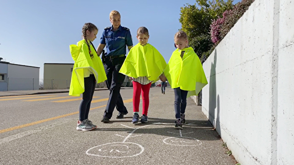 Verkehrsinstruktion mit 3 Kindern und der Stadtpolizistin