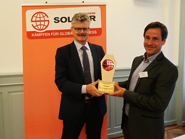 Gemeindepräsident Marco Rupp nimmt die Auszeichnung der Solidar Suisse entgegen.