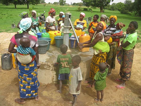 Glückliche Dorfbevölkerung am neuen Brunnen