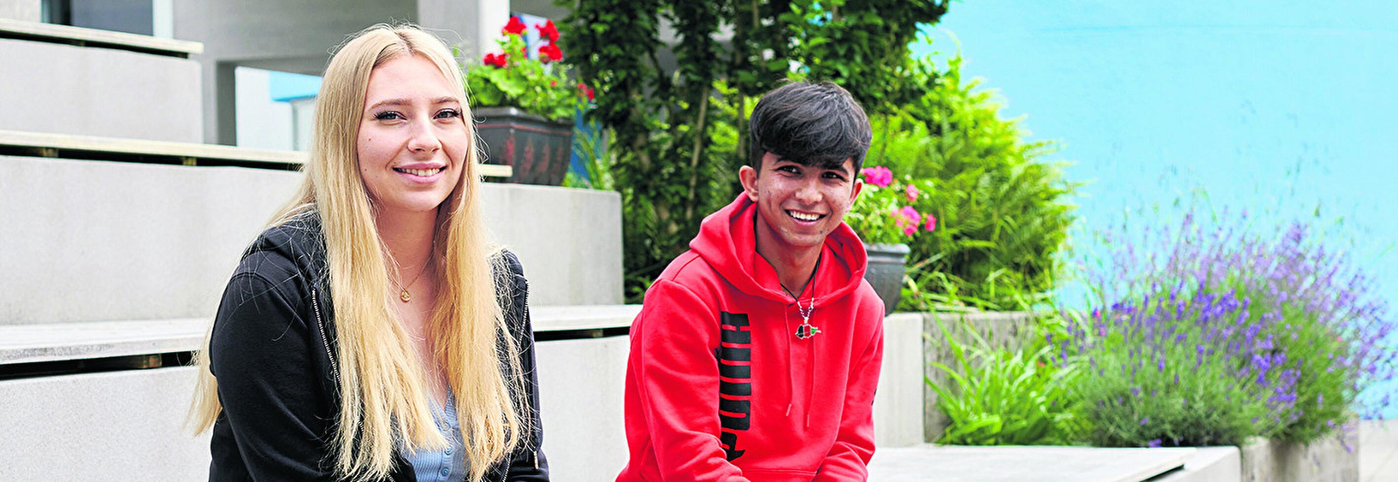 zwei junge Erwachsene sitzen auf einer Bank