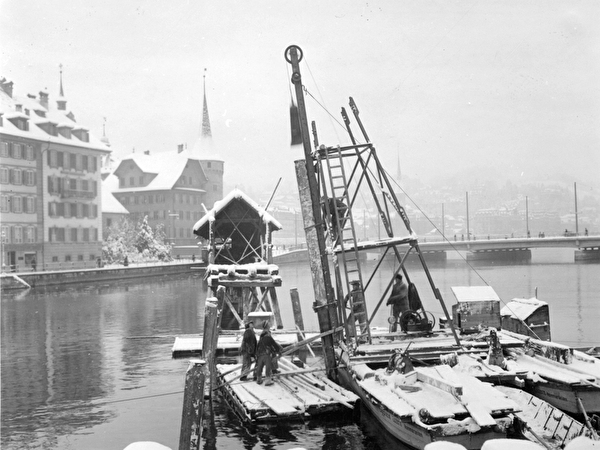 Schwarz-weiss-Foto, Einrammen eines Brückenfahls im Winter