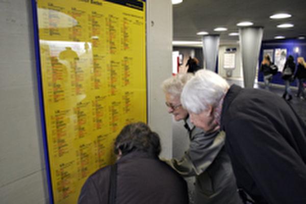 Mehrere ältere Damen studieren einen Zugfahrplan