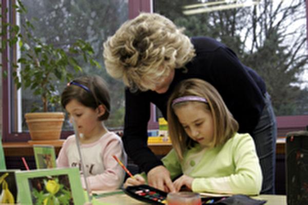 Kleine Kinder beim Malen mit ihrer Lehrerin