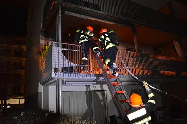 Feuerwehrleute beim Betreten des Balkons über eine Anstellleiter mit dem Schnellangriff.