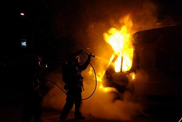 Löschtrupp bei der Brandbekämpfung am Fahrzeug.