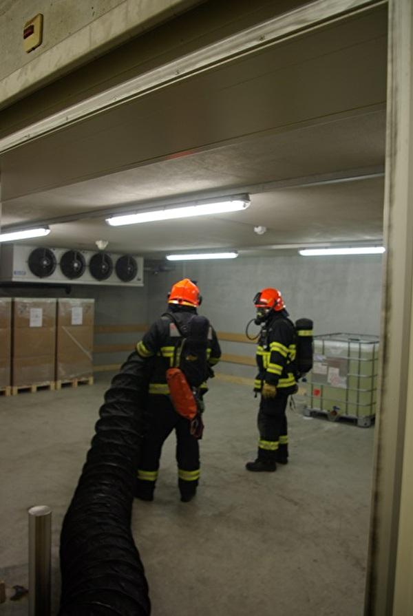 Die Feuerwehr beim Absaugen des Rauches in einem gefangenen Raum mittels Auer-Lüfter und unter Atemschutz.