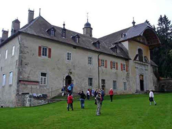 Photo d'un chateau avec des personnes devant