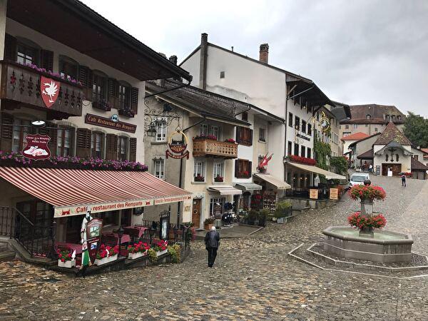 Sicht auf Dorf mit Brunnen in Gruyères bei Regen