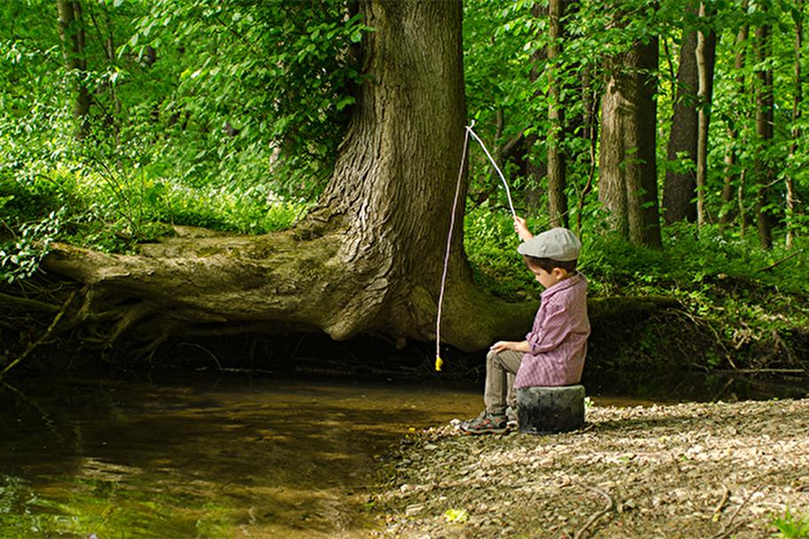 Junge an einem Bach beim Angeln