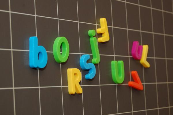 Magnetbuchstaben hängen an einer Wandtafel