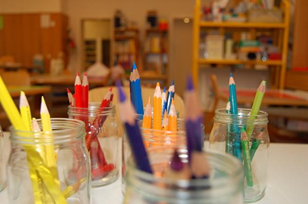 bunte Farbstifte stehen in Gläsern
