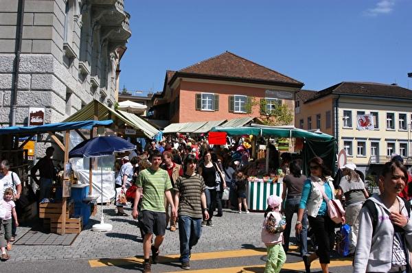 Menschen schlendern durch Marktstände