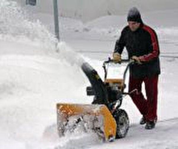 Bild eines Mannes welcher Schnee fräst