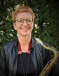 Frau mit Brille und Saxophon lächelt