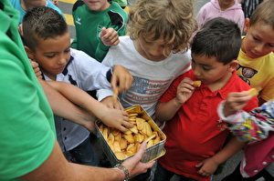 Lehrer verteilt Kekse an Kinder
