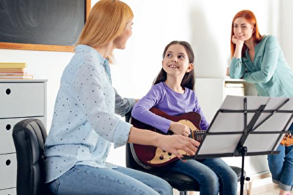 Musiklehrperson mit Kind mit Gitarre im Hintergrund eine Frau