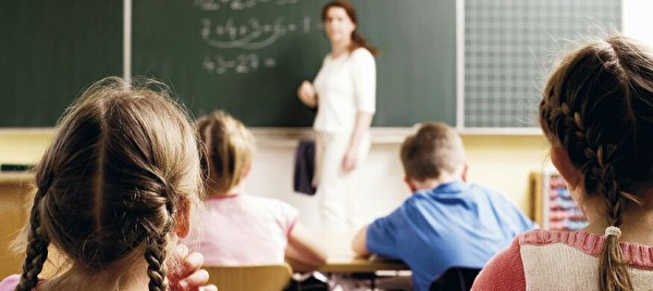 Schülerinnen und Schüler im Unterricht mit Lehrperson an der Tafel