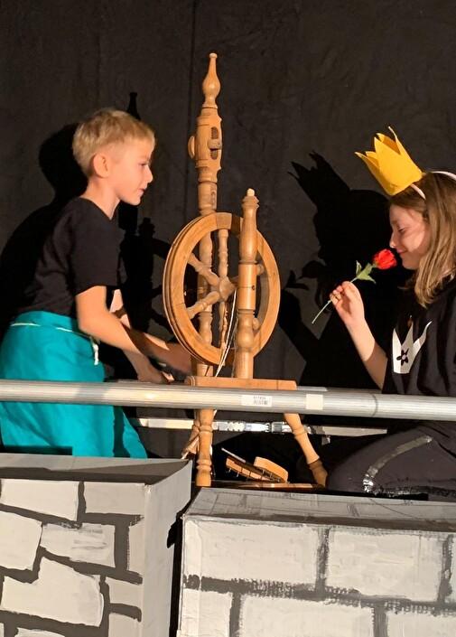 Mädchen und Junge am Spinnrad