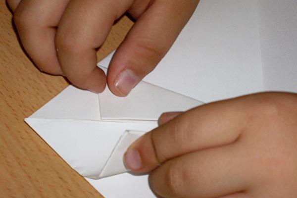 Kinderhände falten ein weisses Blattpapier