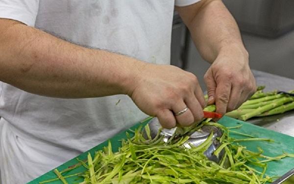 Mann schält Gemüse