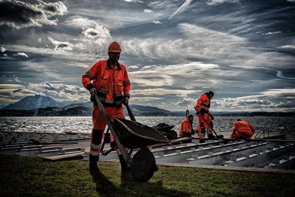 Werkhof-Mitarbeiter montieren den neuen Holzliegerost in der Badi Seeliken. (Foto: Christof Theiler)