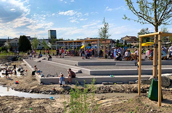 Die Quartierbevölkerung nimmt den neuen Quartierplatz Göbli bei Wurst und Brot in Beschlag. Die Kinder werken schon am wieder geöffneten Arbach. Das Grün wird in den nächsten Monaten zurückkommen.