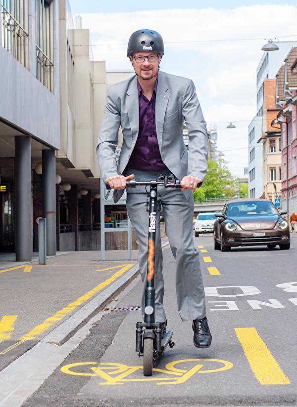 Stadtrat Urs Raschle auf einem E-Trottinett von flash