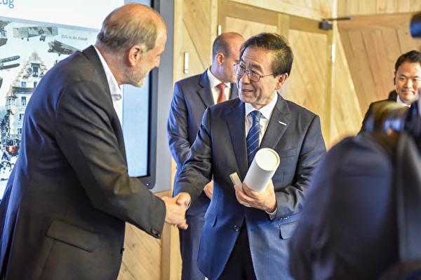 Der Bürgermeister von Seoul bekommt von Dolfi Müller eine Flasche Kirsch und ein Victorinox-Messer überreicht