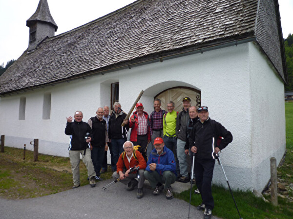 Gruppe versammelt sich vor einer Kapelle für ein Gruppenfoto