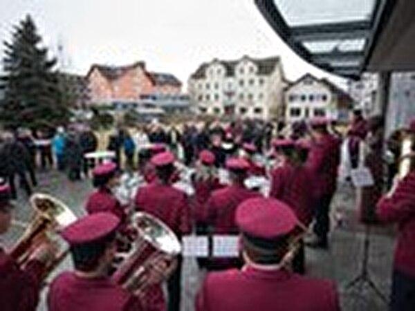Im Vordergrund stehen die Musikanten unter dem Dach des Gemeindehauses und dahinter die Bevölkerung