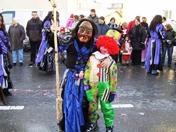 Hexe die einen kleinen Clown umarmt