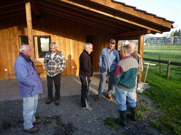 Gruppe Männer der Gruppe Natur 60+ stehen vor einem Holzhaus