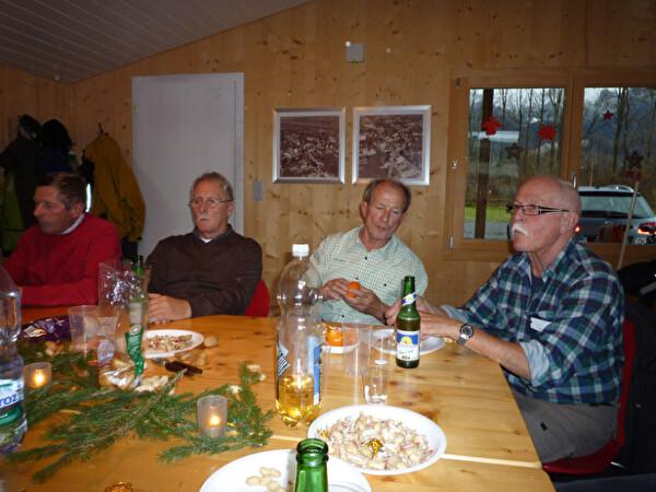 Die Mitglieder sitzen um einen Tisch herum an Nüssli und Mandarinen essen