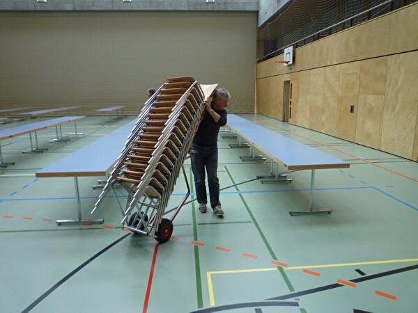 Stühle werden von Helfern auf einem Rollwagen transportiert